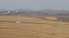 Мост Дружбы, соединивший КНДР с РФ. Поля КНДР в пойме р. Туманная — на переднем плане, посёлок Хасан, Россия, расположен на левом (дальнем на снимке) берегу реки. Белая башня слева — на китайской территории.